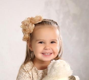 Фотография милой девчушки с игрушкой.