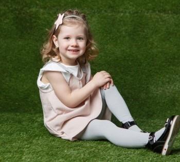 Фотография весёлой малышки на зелёной траве.