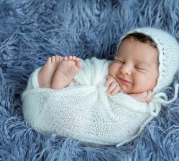 Фото улыбающегося спящего младенца. Лариса Дубинская. Фотограф новорожденных в Днепре.