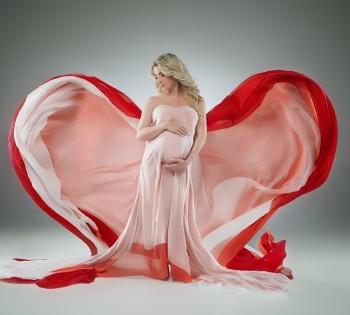 Беременная девушка в шикарном платье с развивающимся шлейфом