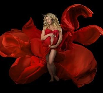 Беременная девушка в потрясающем красном платье со шлейфом.