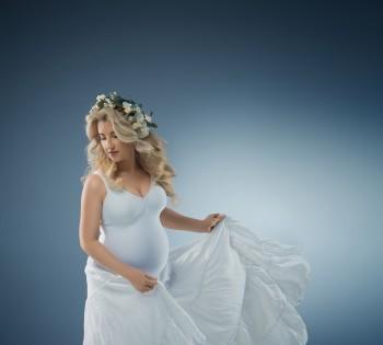 Беременная девушка в нежном платье и венке.