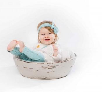 Смеющаяся малышка в деревянной корзинке. Фотосессия детей до года.