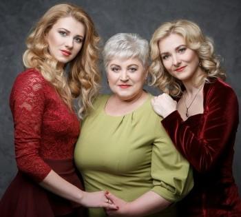 Яркая фотография мамы и двух взрослых дочерей. Семейная фотосессия в студии.