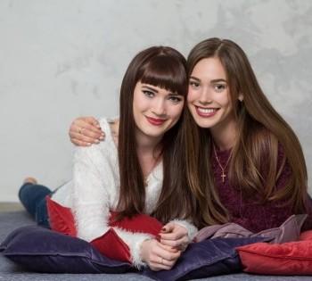 Фотография двух красивых сестёр. Семейная фотосессия в студии.